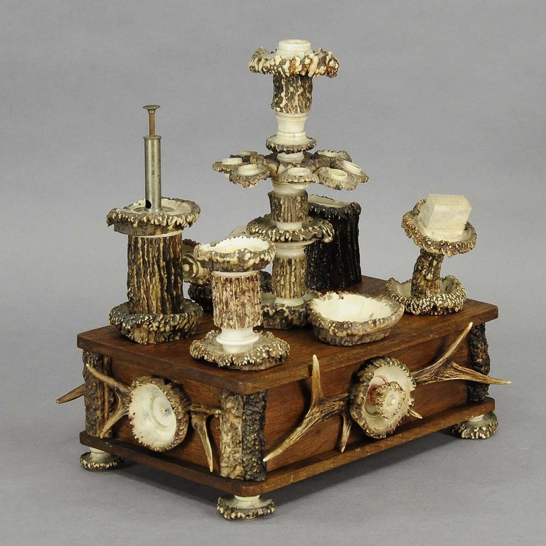 A large elaborately handmade smokers stand. oakwood base with several smoking accessories like ashtray, candle sick, match holder, etc. all hand carved out of original deer antlers. Germany - Black Forest circa 1900.  Measures: Width 12.6