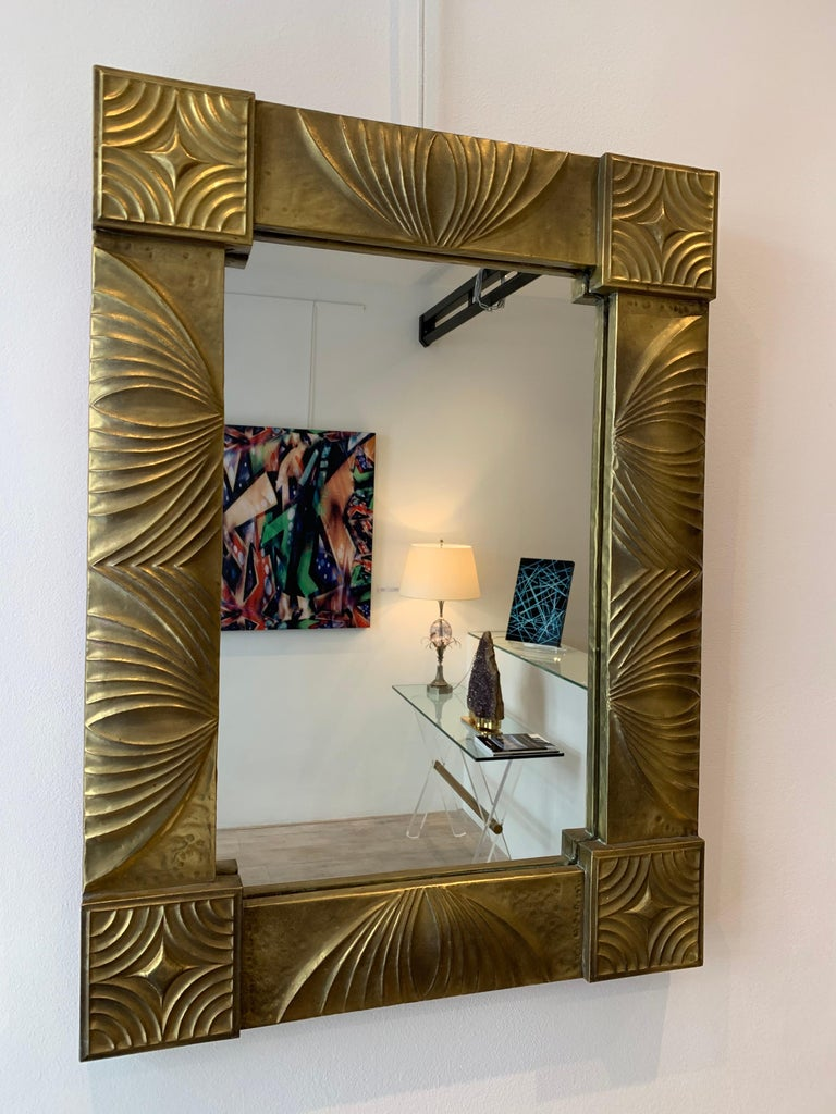 The mirror is worked in the process of repoussé, which means the metal is worked from the back.