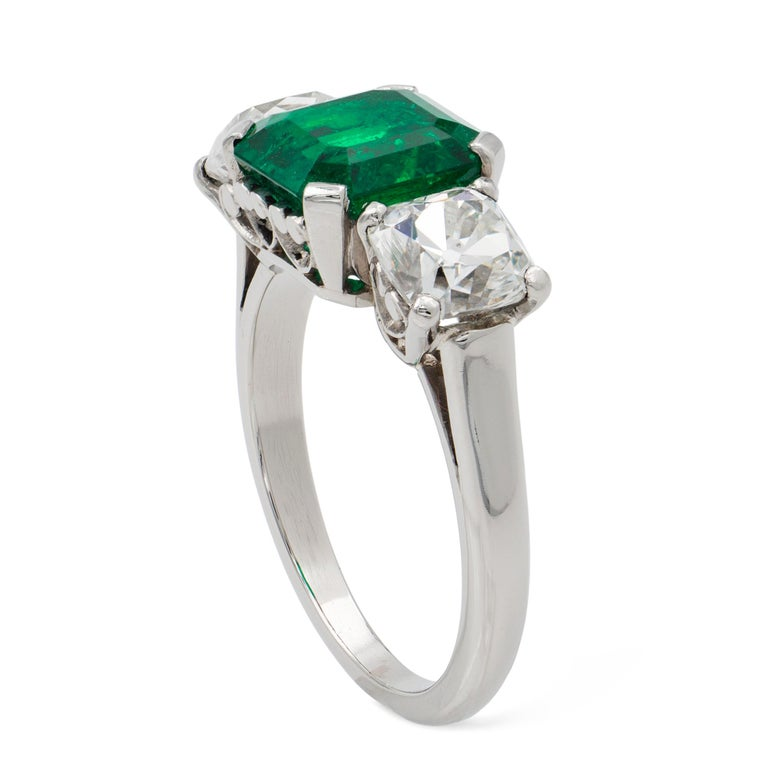 An emerald and diamond three stone ring, the octagonal-cut emerald weighing 2.44 carats accompanied by GCS Report stating to be of Colombian origin, set between two modern Peruzzi-cut diamonds weighing 1.02 and 1.08 carats, all mounted in platinum