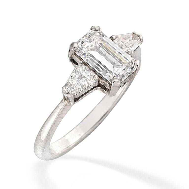 A single stone solitaire diamond ring, the emerald-cut diamond weighing 1.47 carats, of F colour, VS1 clarity, GIA certificate, four claw-set to the centre of two tapered baguette-cut diamonds, estimated to weigh a total of 0.50 carats, claw-set to