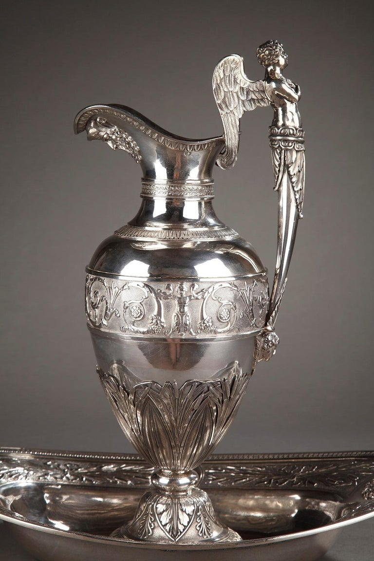 A silver ewer provided with a winged putto-shaped high handle resting on an angel head. A wide frieze with an alternation of Cupids and flowery foliages on matting background decorates the paunch and friezes of water leaves adorn the collar of the