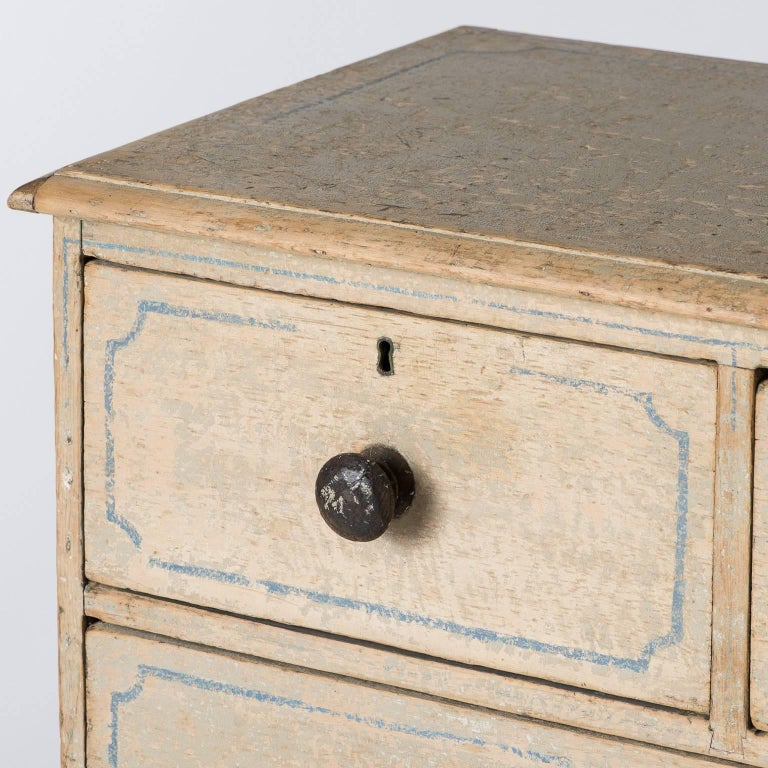 """This charming English cottage chest has a nice patina with pale grey original paint and traces of blue decorative trim on the drawers as well as the top and sides. It is in great condition and provides ample storage.  Measures: 35"""" high 35.5"""""""