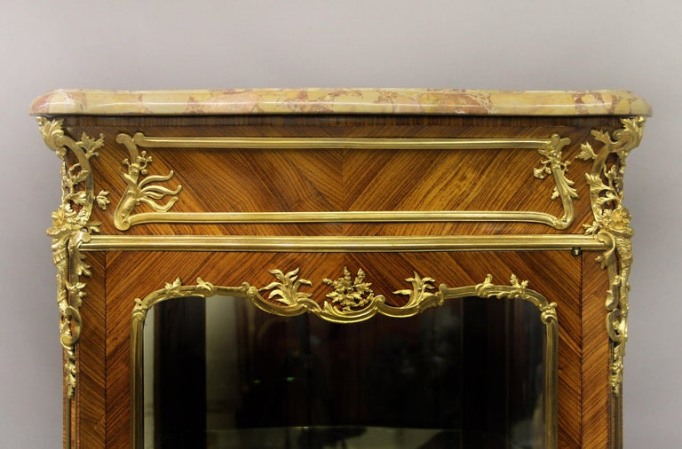 An excellent late 19th century Louis XV style gilt bronze mounted vitrine by Joseph Zwiener  Joseph Zwiener  The serpentine-shaped brèche d' alep marble top above a single centered glass door, flanked to each side by a conforming panel, the
