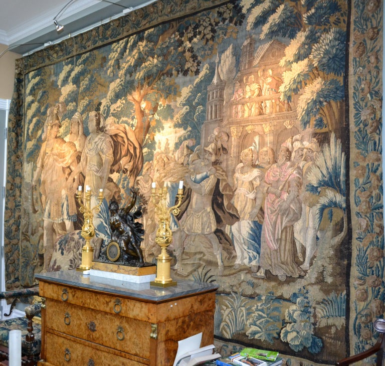 A spectacular Flemish 17 century combined verdure and mythological handwoven wool tapestry in a simple palette of beige, green, brown and blue, framed with a complete floral border and its original protective burlap backing .Combining romanticism,