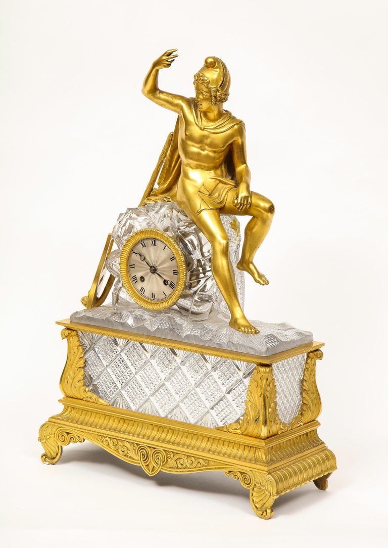 An exquisite French Empire ormolu and cut-crystal clock, c. 1815, attributed to Baccarat.  Made from the finest quality mercury gilding ormolu, this clock depicts an allegory seated on a rock, cased with carved precious cut-glass panels in the