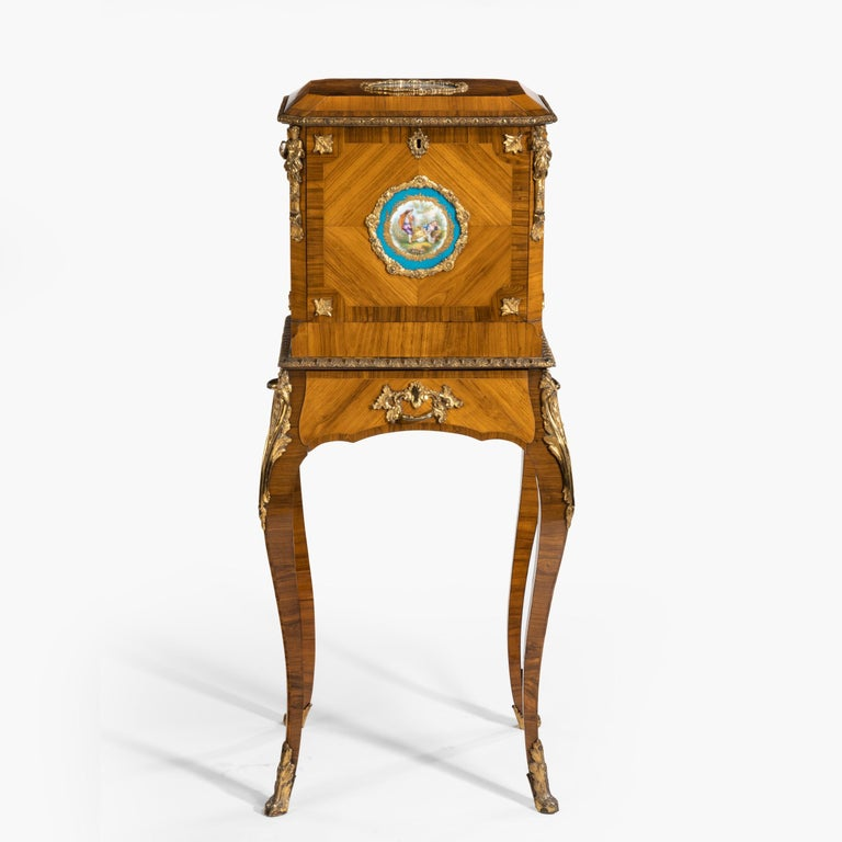 An exquisite jewel casket in the Louis XV Manner  Employing a finely grained book-matched tulipwood, the whole extensively crossbanded with kingwood having gilt bronze mounts and inset with Sèvres style Porcelain plaques. The hinged top lifting
