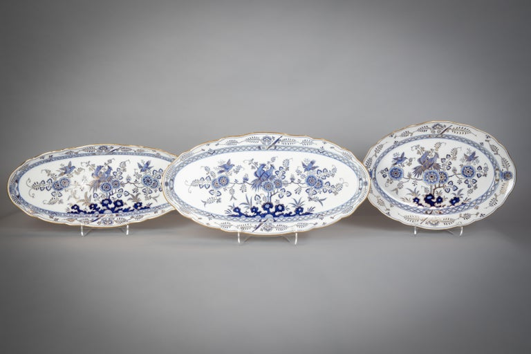 Each piece painted in underglaze-blue and heightened in gilding with an exotic bird perched upon peony branches, comprising: an oval soup tureen, cover and two stands, an 18