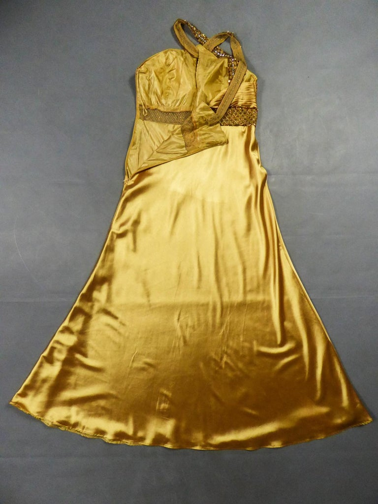 Circa 1980 France  Elegant Music-Hall evening dress in gold Duchess satin embroidered with sequins from the 1980s. Large backless cleavage with crossed straps and embroidered with sequins and rhinestones on cream tulle. High-waisted bustier with