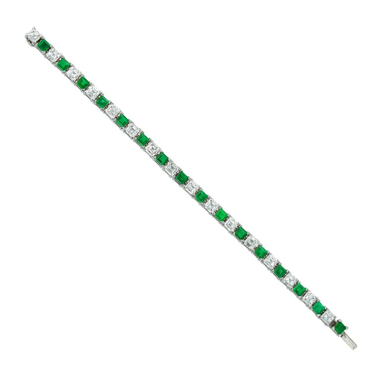 An important emerald and Assher-cut diamond line bracelet by Asprey, consisting of sixteen Assher-cut diamonds weighing 8.44 carats in total, alternately-set with sixteen square-cut emeralds weighing 4.58 carats in total, all four-claw-set in