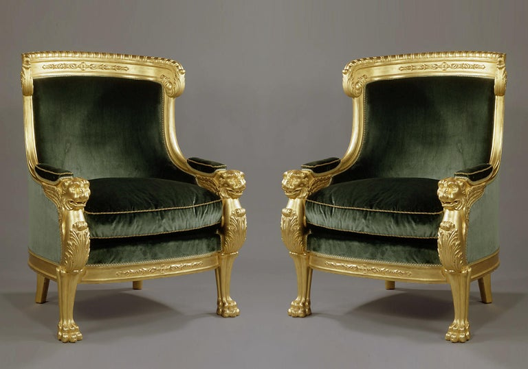 An important pair of Empire style carved giltwood tub chairs with green velvet upholstery.  French, circa 1850.  An important pair of empire style carved giltwood tub chairs with green velvet upholstery. The lion monopedia side supports feature