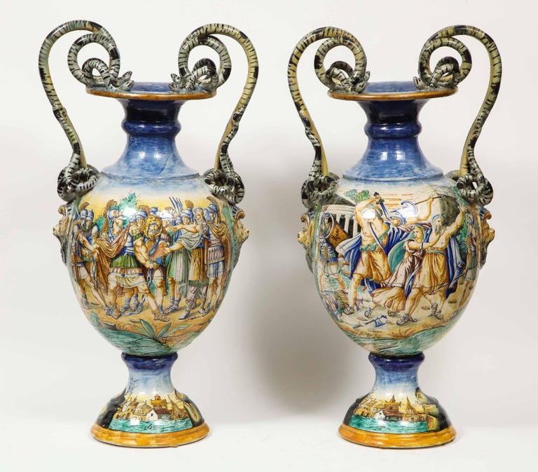 An Imposing pair of large antique Italian Majolica snake-handled vases, late 19th century.  With very fine hand painted classical and biblical scenes and grotesque faces in relief to the sides beneath each detailed snake handle.  Similar to work