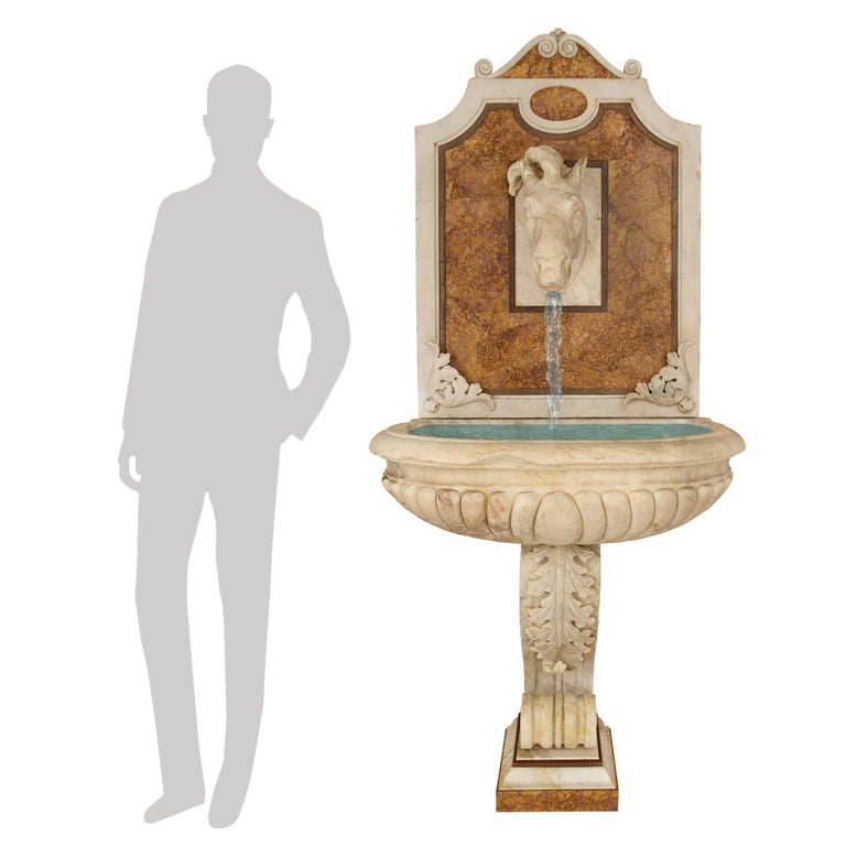 An exquisite Italian 19th century white Carrara and Brocatelle d'Espagne marble fountain. The wall mounted fountain is raised by a square Brocatelle d'Espagne base below a lovely stepped design. The most decorative scrolled central support displays