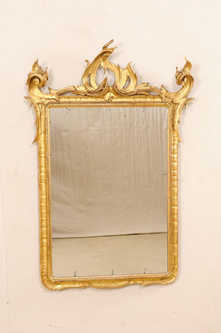 An Italian carved and giltwood mirror from the early 20th century. This antique mirror from Italy is fabulous modern interpretation of Baroque design. It has an overall rectangular-shape with a richly carved crest in Baroque style with a more