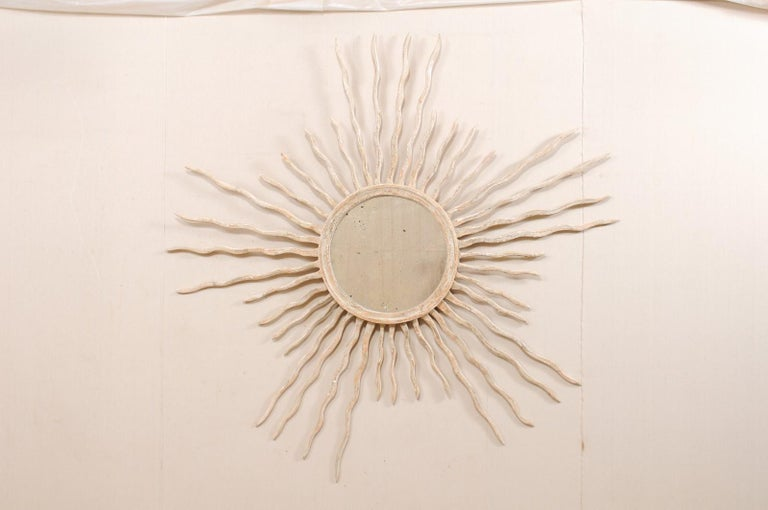 A large sized Italian round mirror with sunburst surround. This custom mirror from Italy, designed by an artisan crafter, features a round-shaped and antiqued center glass, with is set within a wood surround which bursts with rays extending outward