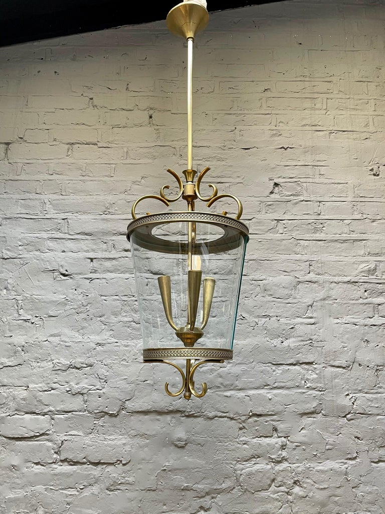 A mid-20th century brass and curved glass lantern, with a scrolled canopy and lattice design frame. The long stem with typical midcentury style light branch interior.  Lantern size without drop stem 56cm H x 31cm W.