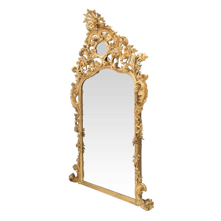 An exceptional quality and large scaled Italian, early 19th century Baroque giltwood mirror. The bottom of the mirror has a mottled frame flanked by stately 'C' scrolls on each end. The mottled frame continues on both sides with a wraparound foliate