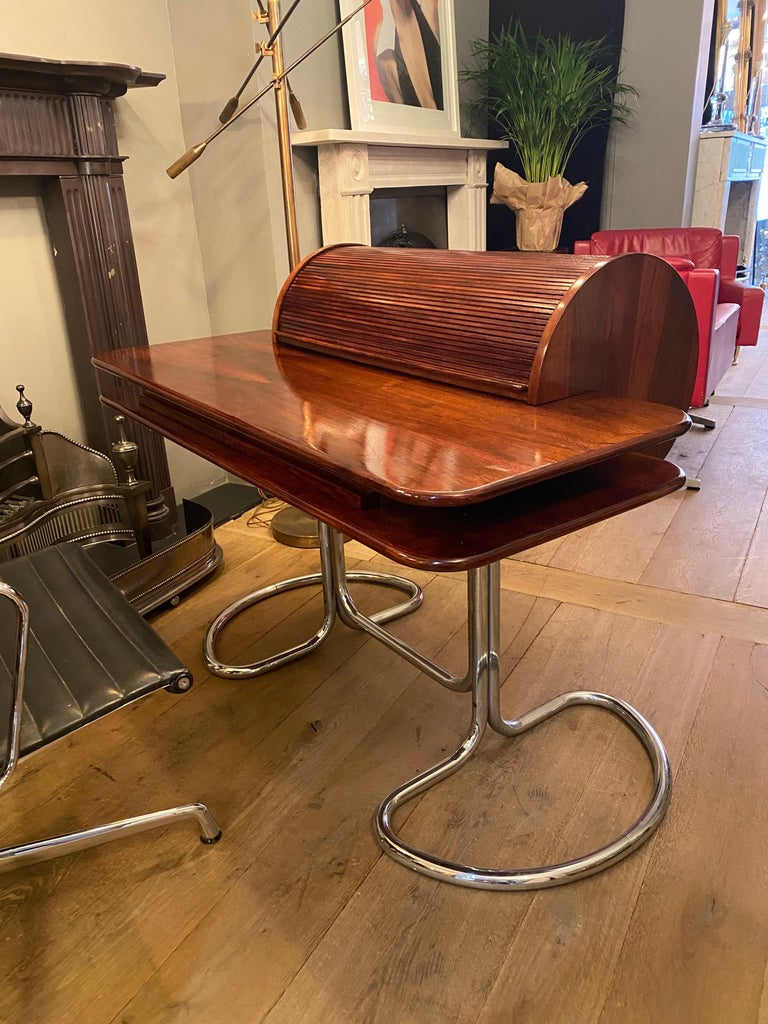 A superb example of this Iconic Italian desk manufactured by Bernini and designed by Giotto Stoppino. Supported on tubular chromed legs, the rich wood top with rolling tambour, which reveals the original trays for stationary. Two discreet drawers