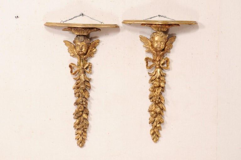 An Italian pair of carved and giltwood wall fragments, with top shelf, from the early 19th century. These antique pair of architectural wall fragments from Italy have been hand carved and gilt, featuring a putti at top, followed in vertical