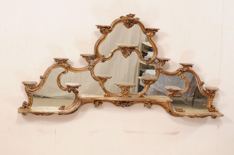 An Italian Rococo style large-sized tiered carved and gilt wall shelf with mirror from the 19th century. This antique étagère (shelf) from Italy has been exquisitely carved in a rocaille and floral motif, with gilt finish and mirrored back. Fourteen