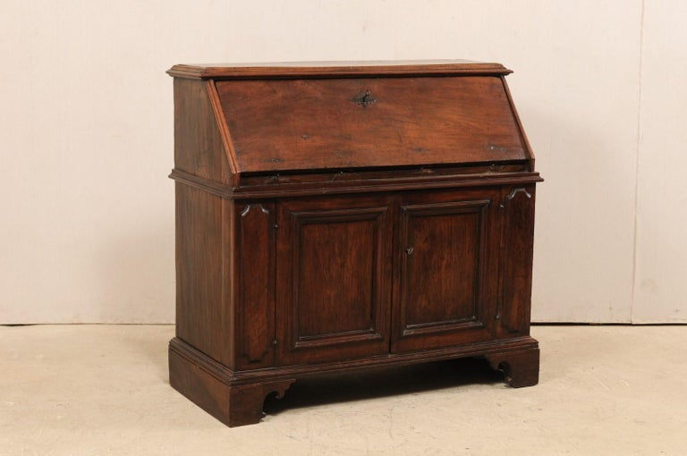 A handsome Italian drop-front secretary cabinet from the 18th century. This antique bureau of walnut wood from Italy features a slanted fall front door, which opens to reveal a nice writing surface and interior display of six compartments. Below the