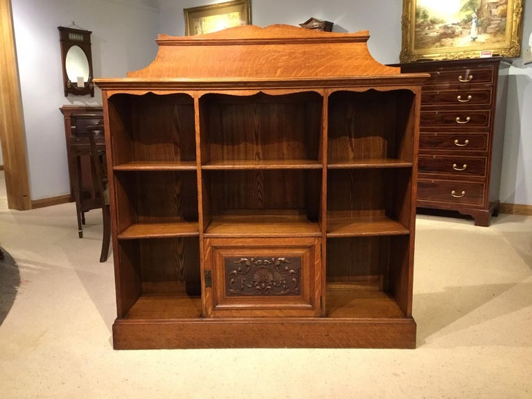 An oak late Victorian period open bookcase. Constructed throughout using the finest quarter sawn oak with beautiful medullary rays. The raised galleried back above a solid rectangular oak top and with five adjustable oak shelves and hinged cupboard