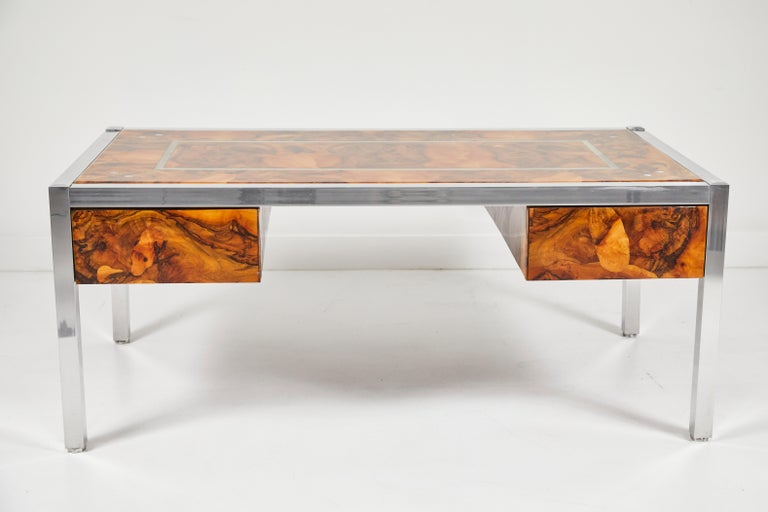 A striking olive burl desk with aluminum legs and accents. A layer of resin encapsulates the desk revealing the distinct patterns in the burl wood. The desk has 2 drawers, one on either side and rests on aluminum legs. A perfect accent for any