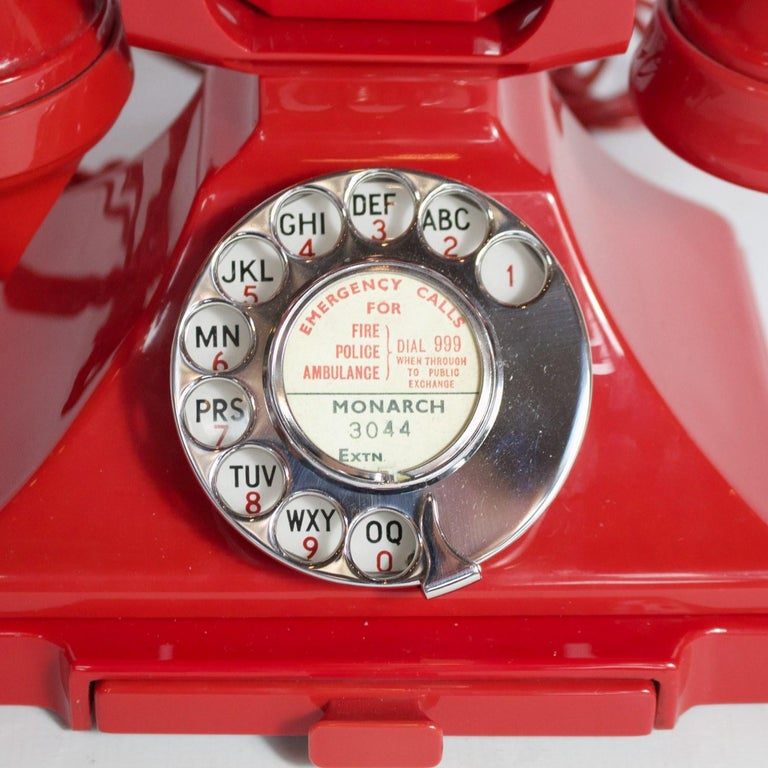 An original GPO 200 series telephone. Red Bakelite with braided handset cord. Integral drawer and registered number to face. 1/232. Manufactured by Siemens. Replacement modern bell.  Dimensions: H 15 cm, W 19 cm, D 15 cm  Origin: