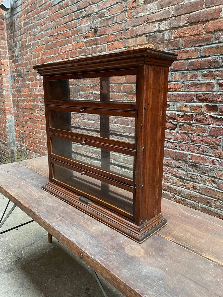 A.N. Russel & Sons oak and glass spool display cabinet. Old counter top general or dry goods store showcase. Solid oak construction with glass panel front and back. Four pullout / pull-out and drop down panels with dowel construction interiors.