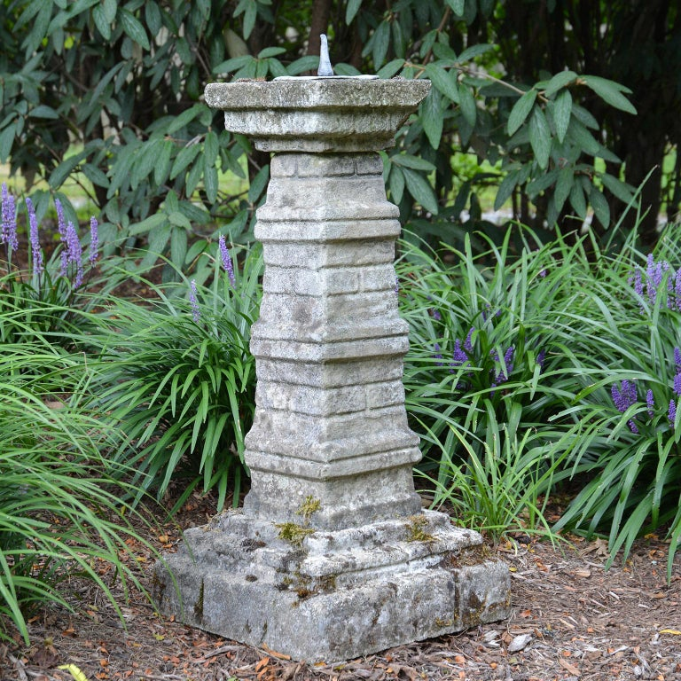 A composition stone sundial pedestal, the body having the appearance of stacked slabs of varying dimension, with lead dial plate.