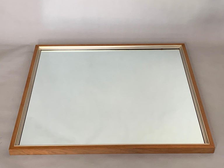 An unusual Paul McCobb mirror in walnut and aluminum from the Calvin collection. Measures approximately 34x36