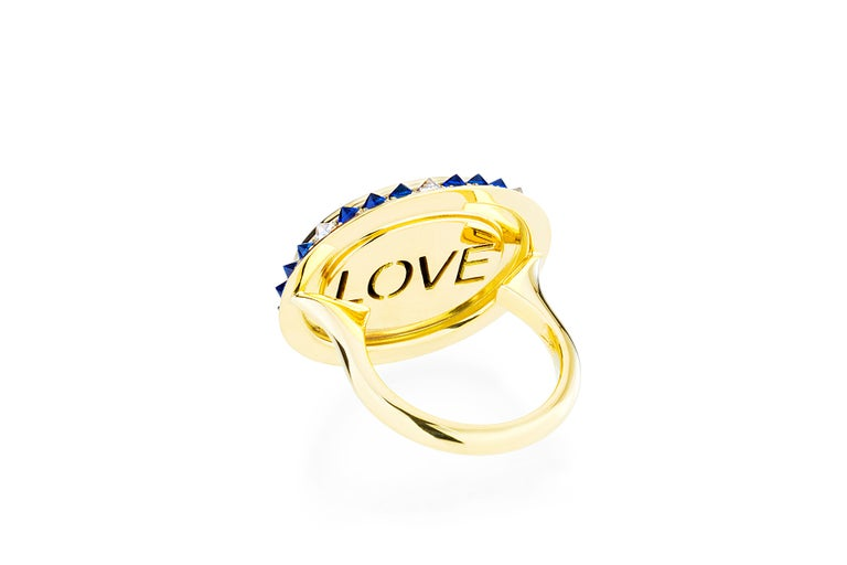 The blue agate cameo in the 'Eye Love Ring' is hand created by a master carver bringing out the colors and depth within the layers of the stone. The cameo is encased in yellow gold, inverted diamonds, and sapphires. As in every piece of the Eye Love