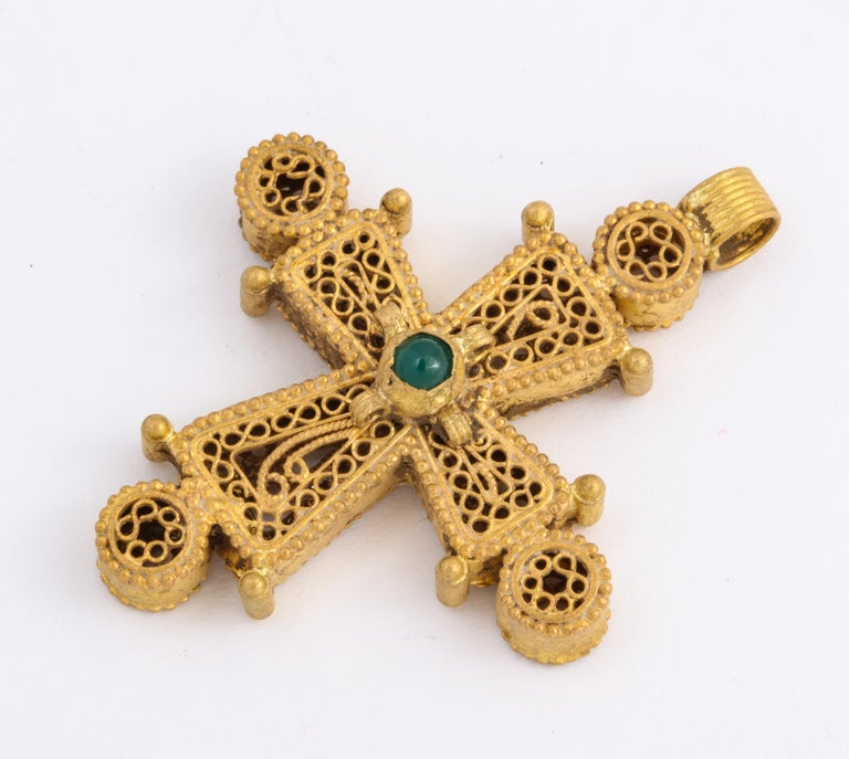 A high karat rare gold Byzantine cross with beautiful open work and circular scroll work is centered by an emerald of the same period. Tiny baubles of gold are placed at each cross end and round the gemstone. The cross was made  approximately one