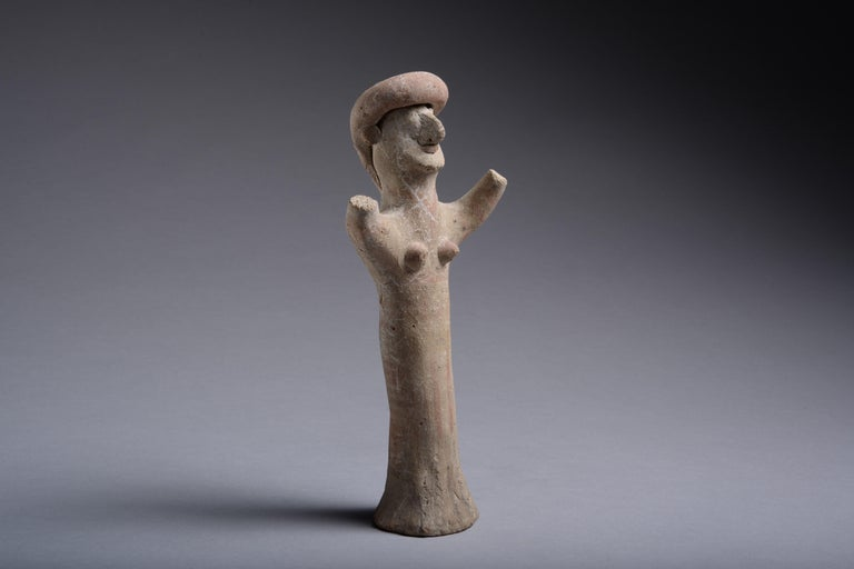 A Cypriot terracotta figure of a goddess or worshiper, dating to the Archaic Period, 7th-early 5th century BC.  Standing on a flared base, with a long, cylindrical body. She wears a large headdress and raises her arms to the sky, her ears