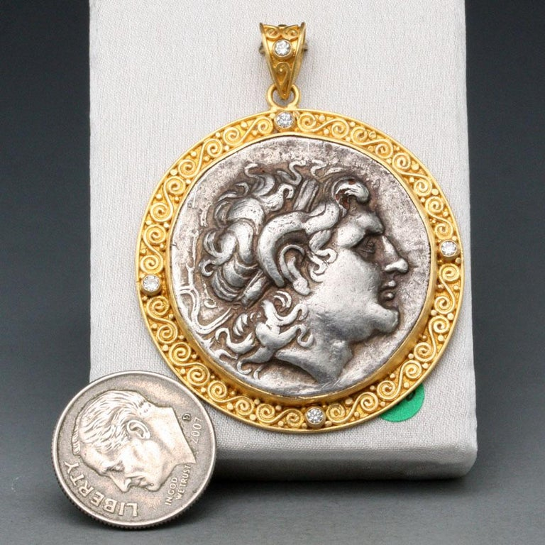 A high-grade authentic ancient tetradrachm coin from Thrace (a historical region which now encompasses parts of Greece, Bulgaria and Turkey) with a depiction of Alexander the Great  is set in a handmade 22K gold multi-spirals bezel with five 1.8 mm