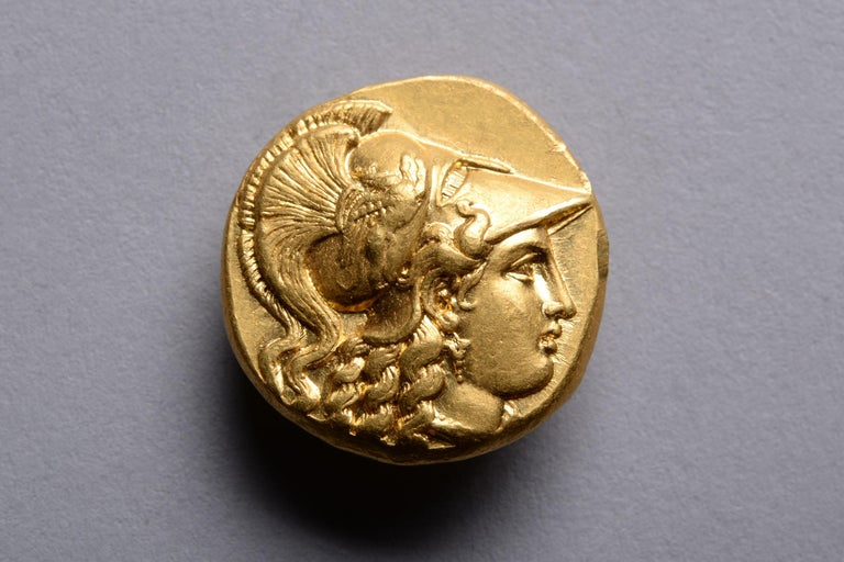 A gold stater issued in the name of King Philip III of Macedon. Struck at the Babylon mint, 323 - 317 BC.   The obverse with the head of Athena, wearing a single drop earring and Corinthian helmet decorated with a charging griffin below an