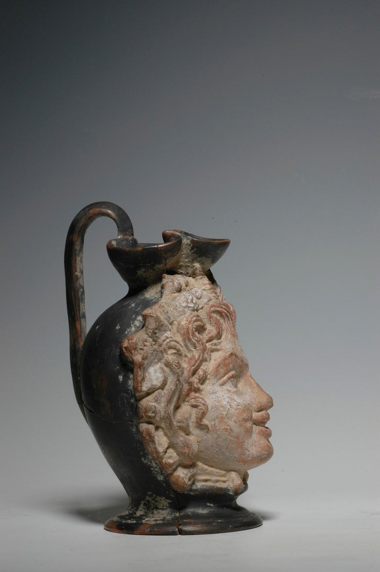 Western Greek trefoil head vase with a very lively face of a faun and well preserved polychrome, circa 4th century BC. The vase is actually a trefoil oinochoe with a handle at the back of the head. A very unusual and rare piece. Provenance: ex. the