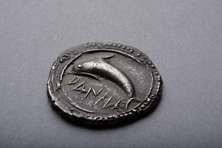 Silver drachm from Zankle, Sicily, circa 520-500 BC.  The front of the coin with a leaping dolphin, swimming into the scythe shaped harbour of Zankle. The inscription reading:  Dankle  The back with a scallop shell within a grid shaped incuse