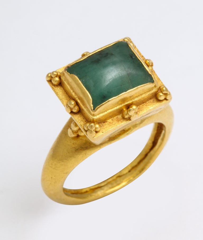A rare 22 Kt. gold British ring with a circular shank is the stage for a trumpet bezel and square emerald stone. The setting is surrounded with elegant granulated decoration. The ring is gorgeous and likely belonged to a Medieval noblelady from the