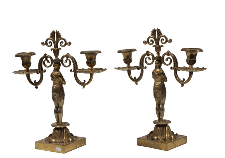 Pair of candleholder is an original decorative object realized at the end of the 19th century by French manufacture.  The artwork has two arms in gilded bronze with a capital base surmounted by a sculpture of a female figure that supports the