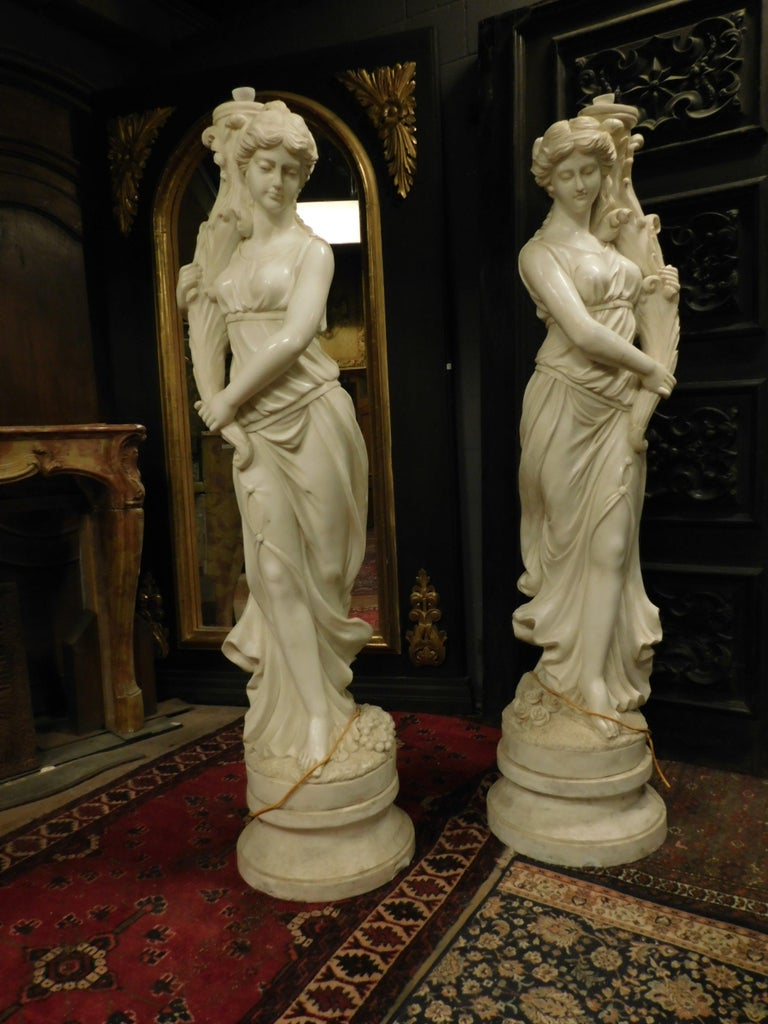 Ancient pair of statues (already with pipe and attachment for fountains) hand carved in white marble, full-length portraits of muses supporting the gush of water, made in the 1900s in Italy. Precious marble, suitable for a luxury garden, or in a