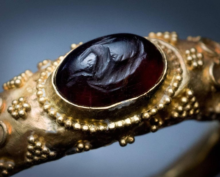 A museum quality ancient Roman gold ring, circa 400 AD.  This hollow ring is bezel-set with a garnet intaglio of Hippocamp – a fish-tailed horse that was considered the horse of Poseidon in Greco-Roman mythology. Poseidon was the god of the sea,