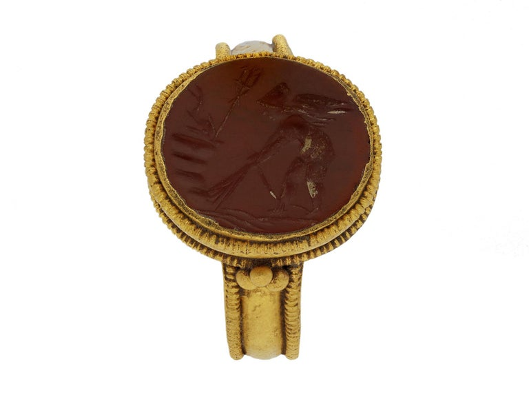 Ancient Roman gold ring with intaglio of Neptune. Set with an oval glass cloison intricate intaglio of a winged figure bowing to Neptune with trident and dolphin, in a closed back Roman set setting with a double border of granulation and flanked by