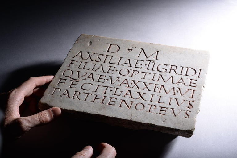 """Roman marble inscription, dating to the 1st century AD.  A finely carved six-line inscription, reading:  """"To the spirit of the departed: Lucius Axilius Parthenopaeus, to his excellent daughter Axsilia Tigris, who lived 21 years, 6"""