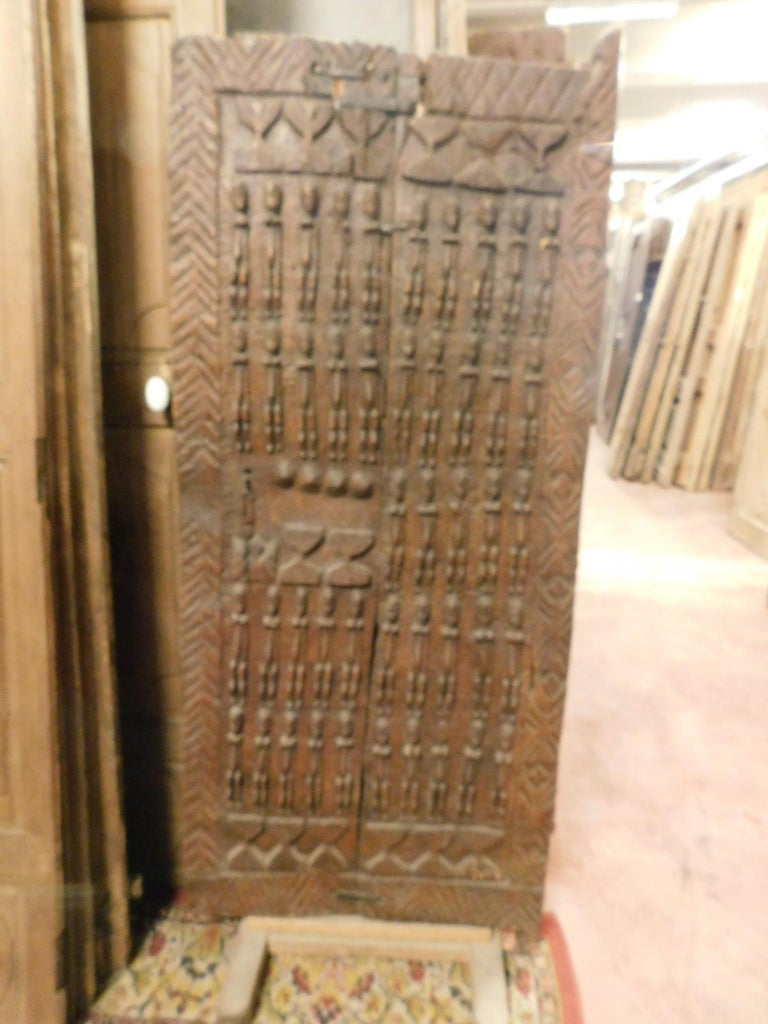 Ancient wooden door of African tribal chieftain, carved with images of outdated enemies to become chief, is small because the subjects had to bow to him to enter his house, very special and rare, usable also as a decorative panel, all carved by hand