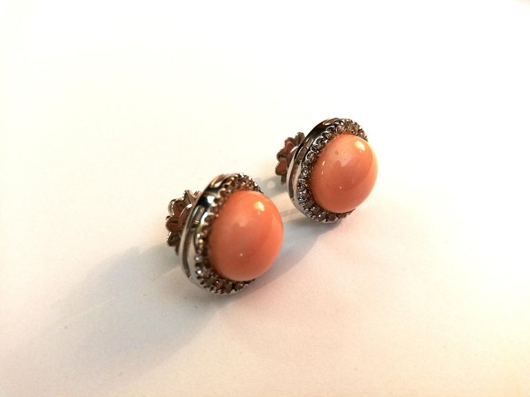 An elegant pair of earrings mounted on 18Kt white gold, embellished with diamonds (1,16Kt) surrounding a light pink coral (3.10gr) in the middle.