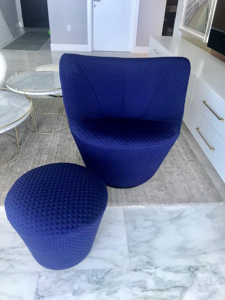Outstanding swivel lounge chair and matching ottoman designed by Pierre Paulin. Modernist design with elegant curves throughout. Offers exceptional comfort with low back design and swivel base feature. Custom woven upholstery in vibrant mood indigo