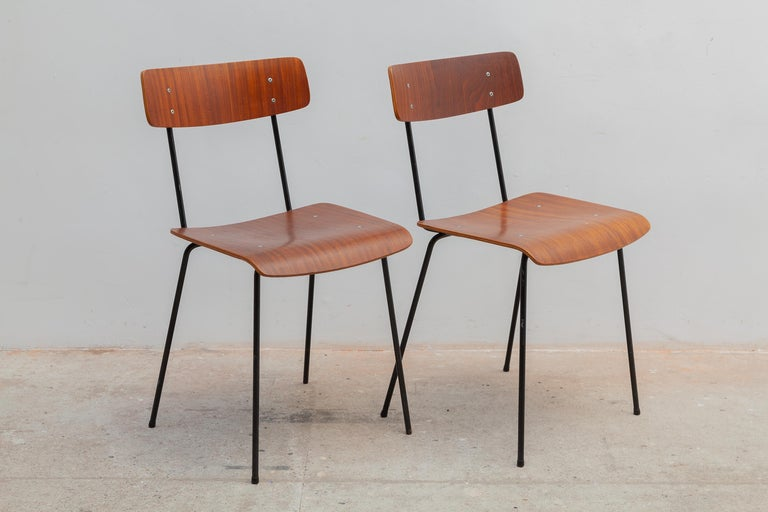 Classic Mid-Century Modern design set of 2 Minimalist plywood dining chairs designed by André Cordemeyer in 1959 for Dutch Industrial Manufacture Gispen. Black lacquered metal frame and teak veneered plywood seat and backrest. Dimensions: 40 W x 78