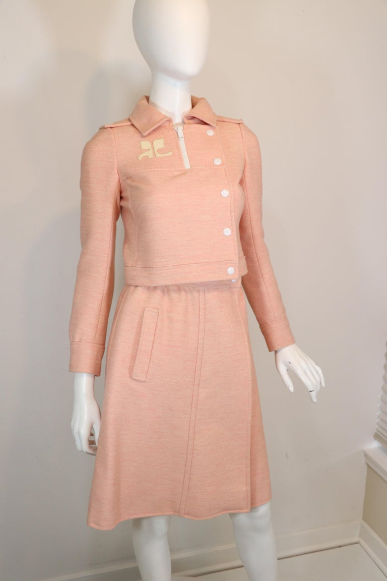 Andre Courreges modernist numbered couture pink wool jacket & skirt set from the 1970's. Jacket features large AC vinyl logo. Large plastic coated half zip and plastic coated snap closure. Wrap skirt with single size pocket. Numbered couture label.