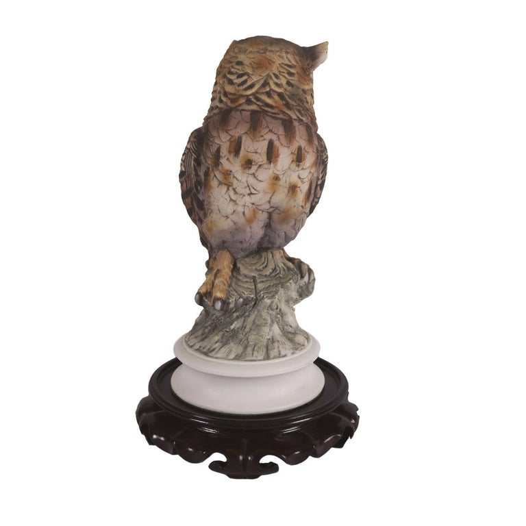 This painted porcelain Great Horned Owl is made by Andrew Sadek. The owl statue stands 15 inches in height and is 6 inches in width. The wooden stand is included as shown.