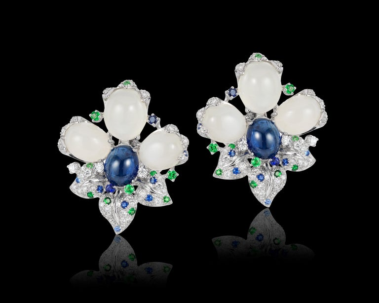 Andreoli Blue Sapphire Moonstone Cabochon Diamond Tsavorite Flower Earrings . These Andreoli earrings features 6 dome cabochon shaped oval moonstones weighing 24.57 carats. Two center dome shaped oval cabochon blue sapphires weighing 8.97 carats.